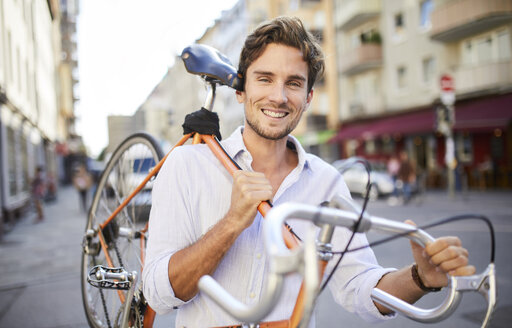 Portrait of smiling young man carrying his racing cycle on shoulder in the city - PNEF01085