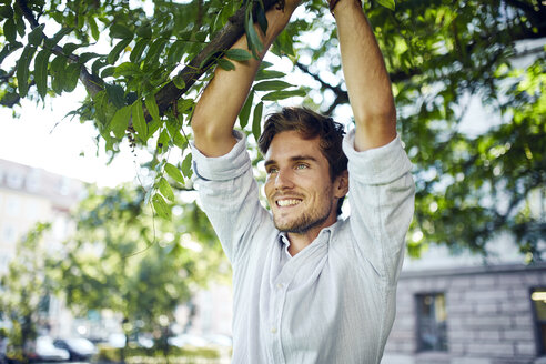 Portrait of smiling young man reaching branch of a tree - PNEF01094