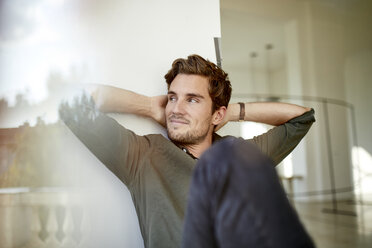 Portrait of young man sitting behind windowpane relaxing - PNEF01103