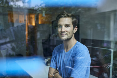 Portrait of content young man behind windowpane in an office - PNEF01106