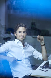 Portrait of successful young businessman behind windowpane at his office desk - PNEF01118