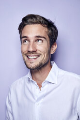 Portrait of laughing young man in front of purple background looking up - PNEF01124