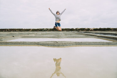 France, Bretagne, Marais salants de Guerande, Woman jumping - GEMF02445