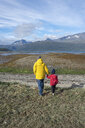 Norway, mother and daughter walking to the Lyngen fjord - PSIF00135