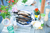 Plate of grilled fish on table with flowers - LUXF02209