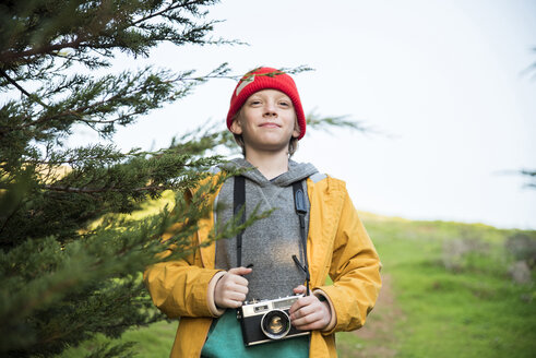 Portrait of boy with camera standing by tree against sky - CAVF52364