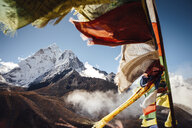 Colorful prayer flags hanging by mountain against blue sky during sunny day - CAVF52379