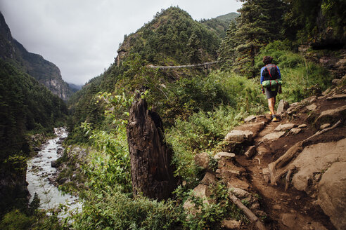 Rear view of hiker with backpack walking on mountain at Sagarmatha National Park - CAVF52394