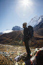 Hiker with backpack standing on mountain against clear blue sky during sunny day - CAVF52403