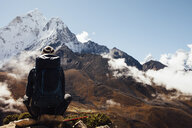 Rear view of hiker with backpack sitting on mountain blue sky at Sagarmatha National Park - CAVF52406