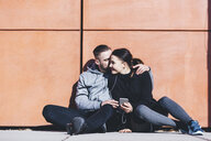 Boyfriend kissing girlfriend using smart phone while sitting by wall on sidewalk - CAVF52418