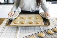 Midsection of woman holding cookies baking sheet over table in kitchen - CAVF52424