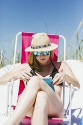 Young woman reading book while sunbathing at beach during sunny day - CAVF52445