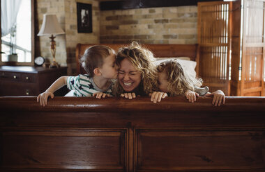 Happy children kissing mother on bed at home - CAVF52454