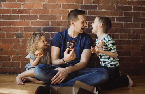 Father with children eating donuts while sitting on floor at home - CAVF52460