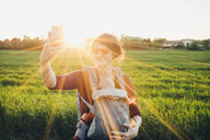 Mother taking selfie while carrying son in baby stroller on grassy field against clear sky - CAVF52472