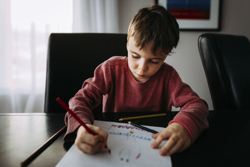 Boy drawing with colored pencil on paper at home - CAVF52484