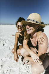 Cheerful female friends crouching at beach during sunny day - CAVF52565