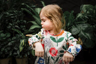 Cute baby girl blowing butterfly on her hand against plants - CAVF52574