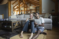 Smiling couple with digital table looking away while sitting in living room at home - TGBF01152