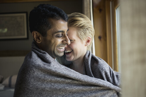 Smiling multi-ethnic couple wrapped in blanket and embracing at home - TGBF01161