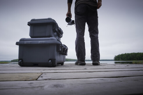 Low section of man holding camera by suitcases on wooden pier - TGBF01263