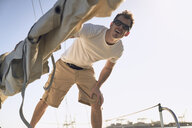 Low angle view of man looking away while standing on sailboat - TGBF01293