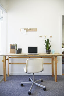 Laptop on desk against white wall in creative office - TGBF01296