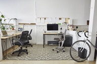 Chairs and computer against white wall in creative office - TGBF01302