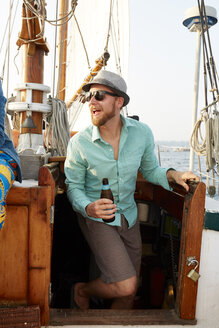 Happy young man holding beer bottle while standing in boat against sky - TGBF01452