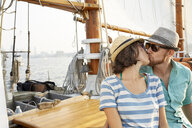 Loving man kissing woman while sitting on boat against sky during summer - TGBF01455