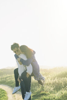 Happy young man giving piggyback ride to woman while hiking - TGBF01563