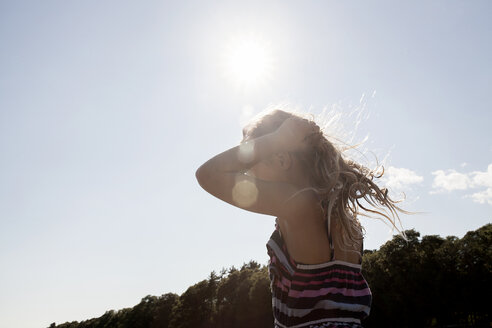 Side view of girl standing with hand in hair against sky during summer - TGBF01569