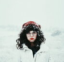 Front view of a young brunette woman on a snowy day in winter - INGF05439