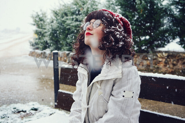 Young nerdy woman enjoying a snowy day outdoors - INGF05454