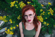 Portrait of young woman with red hair posing against flowers - INGF05460