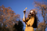 Portrait of a young redheaded woman holding a leaf over her face - INGF05511