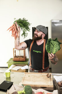 Vegan man choosing vegetables in his kitchen - REAF00349