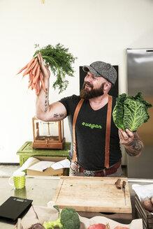 Vegan man choosing vegetables in his kitchen - REAF00349