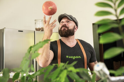 Vegan man playing with a pumpkin in his kitchen - REAF00355