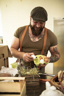 Mature man with delivery service checking eggs, before packing them in cardboard boxes - REAF00373