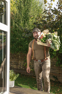 Mature man carrying crate with vegetables in his garden - REAF00388