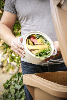 Mature man throwing kitchen scraps into bio-waste container - REAF00394