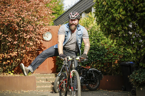 Portrait of happy man switching from motorbike to bicycle - REAF00397