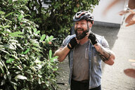 Portrait of laughing man putting on bicycle helmet - REAF00400
