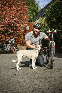 Portrait of smiling man with dog and bicycle - REAF00403