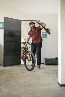 Portrait of man arriving in office with bicycle - REAF00406
