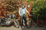 Portrait of man switching from motorbike to bicycle - REAF00415