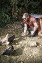 Man in his own garden, man feeding free range chickens - REAF00433