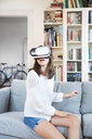 Girl sitting on the couch at home using Virtual Reality Glasses - LVF07515
